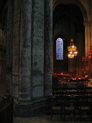 Interior of Chartres Cathedral: dark pillars and vaults, pews, and lit candles